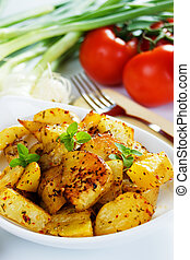 Well spiced roasted potato slices in white plate