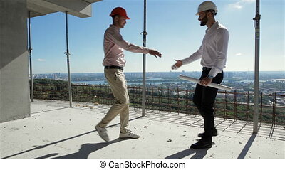 Two builders meet at the building under construction - Two...