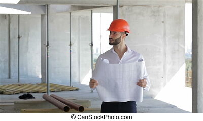 Construction engineer walks through the building under...