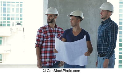 Three builders pose at the building under construction -...