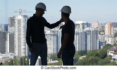 Two builders look at the landscape of high buildings - Two...