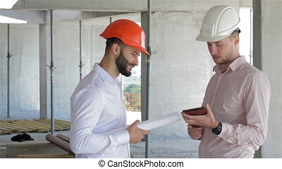 Two builders looking at the digital tablet at the building...