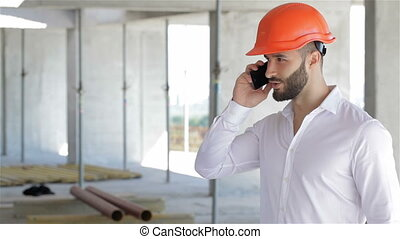 Construction engineer talking on the phone at the building...