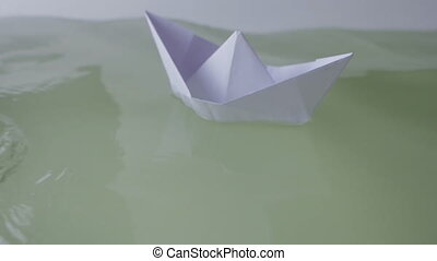 paper boat floating in some water - looping video of a paper...