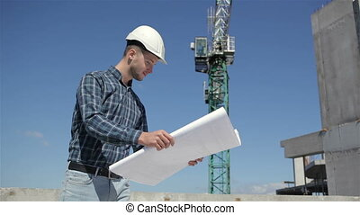 Construction manager look at the sheet with plan of building under construction
