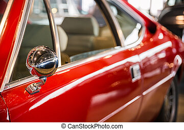 rearview mirror of a red car - Chrome rearview mirror of a...