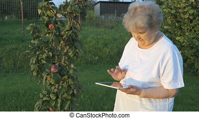 Old woman 80s holding a digital tablet outdoors
