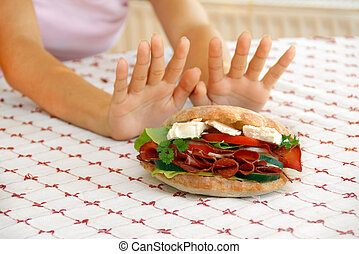Diet - female hands refusing big meat sandwich with ham and...