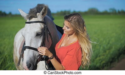 Beautiful blonde girl standing with a horse at a...