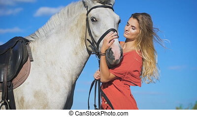 Beautiful blonde girl standing with a horse at a countryside