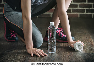 Squat on wooden floor take rest drinking water, fitness...
