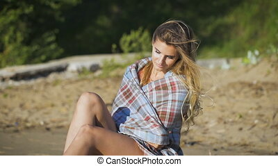 Beautiful girl sitting on wood. Travel and Vacation. Freedom Concept. Sensual blonde beautiful woman