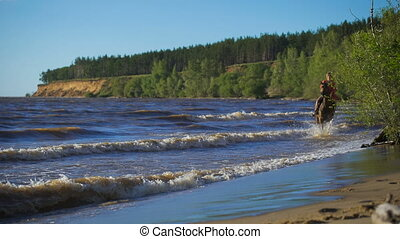 A beautiful blonde young woman riding a horse at a lake