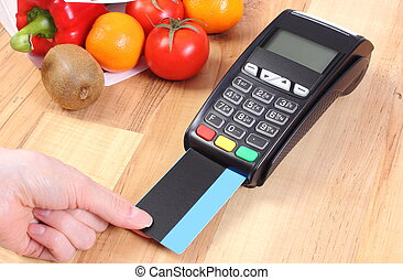 Payment terminal with credit card, fruits and vegetables,...