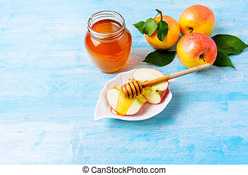 Apple slices with honey on blue wooden background. Rosh...
