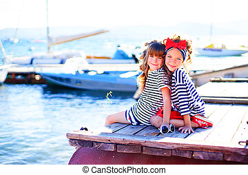 two girls sitting on the dock