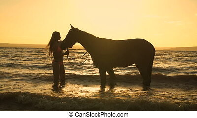 A beautiful blonde young sexy woman standing next to a horse at a lake