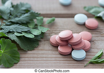herbal medicine concept, pills and plants on wooden...