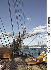 View of a bowsprit of a large wooden sailboat against blue...