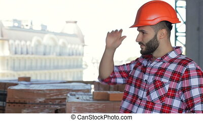 Male builder corrects his hard hat at the building under...