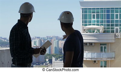 Builder points at the penthouse near the building under construction