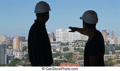 Builder points his hand at the complex of high buildings -...