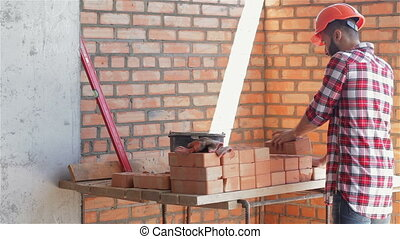 Builder shifts bricks at the building under construction -...