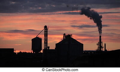 Silhouette of industrial building with smoking chimney