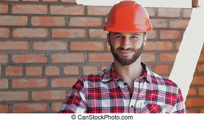 Male builder shows his thumb up - Male builder showing his...