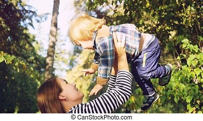 Young brunette mother lifting her son in park having fun...