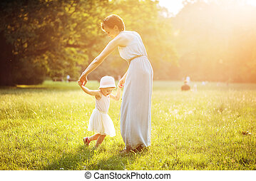 Attractive mother dancing with her daughter on the lawn -...