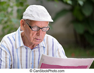 Old man reading newspaper - Senior man with glasses reading...