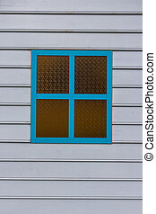 Blue window with glass on white wooden wall