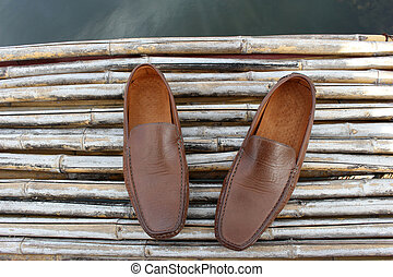 Brown shoe on bamboo wood over pond