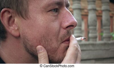 Smoking man with a cigarette in his hand - Smoking person is...