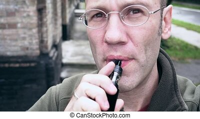Man exhaling e-cigarette smoke cloud from mouth - A man is...