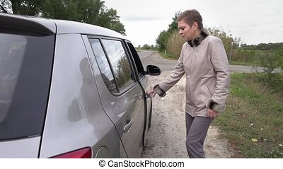 Woman getting into the car after stopping on a rest in the...