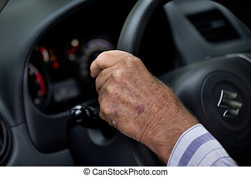 Old man driving car - Close up of old mans hand on steering...