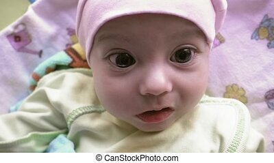 Newborn baby with big brown eyes looking around