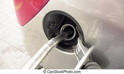Petrol pump filling fuel into a car at gas station - Close...