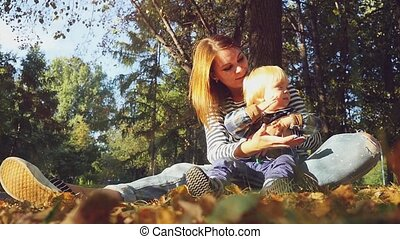 young beautiful mother playing with her baby. Mom and son sitting on the grass in a park in autumn in slowmotion and soap bubbles flying on the background. 1920x1080