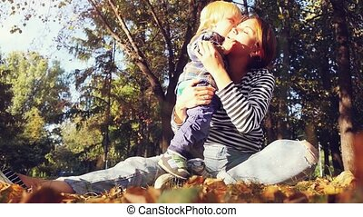 Young mother holds her baby. Mom and son sitting on the grass in a park in autumn in slowmotion. 1920x1080
