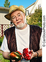 senior man with peppers - Portrait of a smiling senior man...