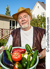 showing a harvest - Smiling senior man with his harvest in...