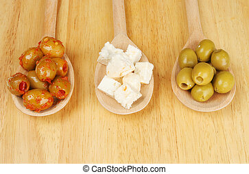 Olives and feta cheese in spoons - Olives and feta cheese in...
