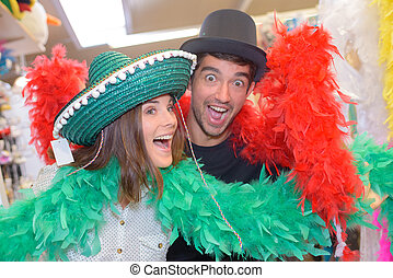 Couple posing in fancy dress hats and boas