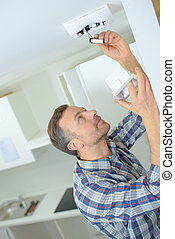 Safety conscious man fitting a fire smoke alarm