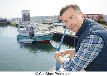 Man leaning on railing on harbour