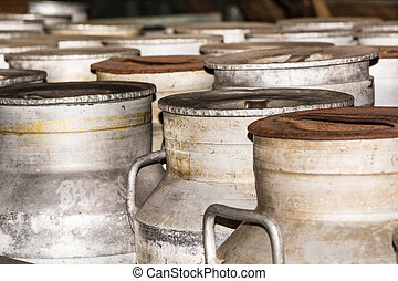 Rusty nostalgic milk cans - Old milk cans in a row on a farm