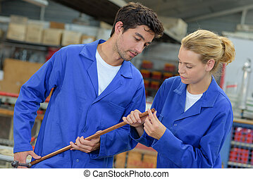 Two young manual workers inspecting copper pipe